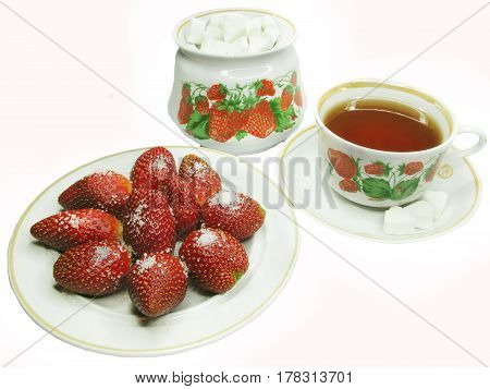 tea with stawberry and sugar on the plate