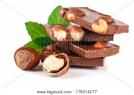 Chocolate with hazelnut and mint leaf isolated on white background.