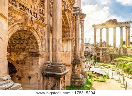 Arch of Emperor Septimius Severus and Temple of Saturn in the distance at the Roman Forum in Rome, Italy
