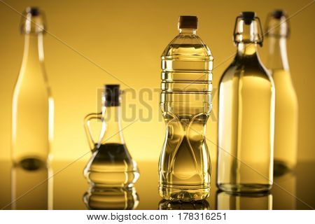 Vegetable oil made from rapeseed in bottles on glass table