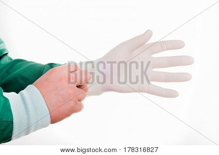 Close up of male doctor's hands putting on sterilized surgical gloves against white background