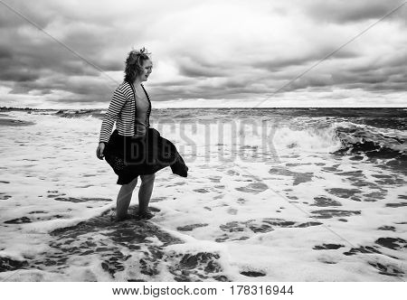 A Young Woman In A Billowing Skirt Stands Among The Stormy Sea With Waves, In Black And White