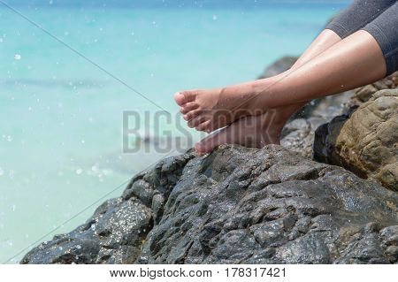 Beautiful woman put feet on the rock at the beach sand and ocean water feet on rock with blue sea background vacation and holiday concept