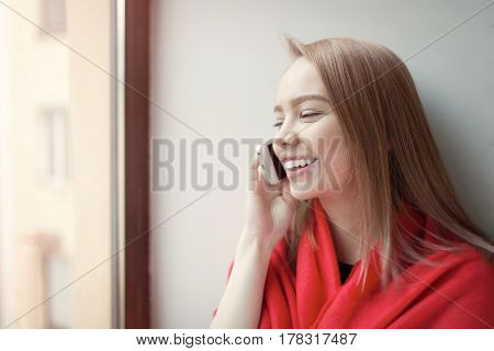 Young Blonde Girl Talking On The Phone Sitting By The Window, Wrapped In A Red Blanket. She Is Happy