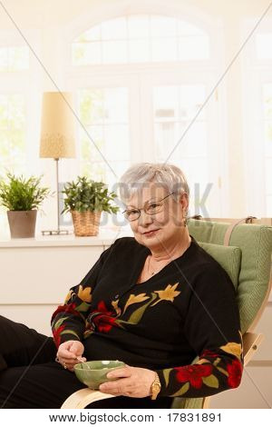 Portrait of senior lady having tea at home, sitting in armchair, smiling at camera.?