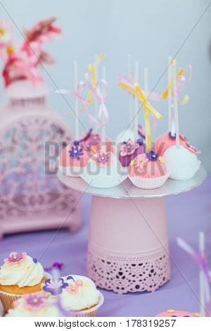 Beautiful composition of children's sweets-cakes decorated with bows and flowers