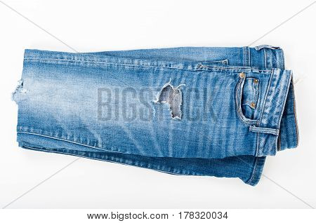 Folded ripped blue jeans on white background. Top view. Fashion concept.
