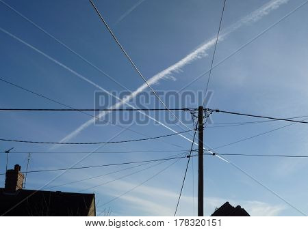 Aircraft vapour trails across telegraph wires and blue sky with rooftops poster