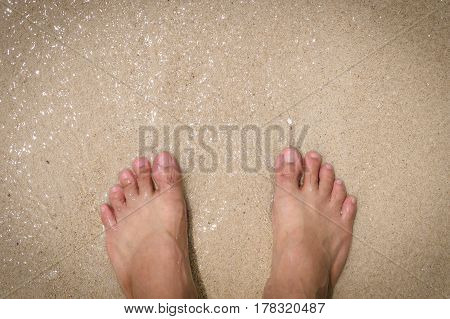 Abstract pair of feet in beach sand and frothy ocean water feet on sand background