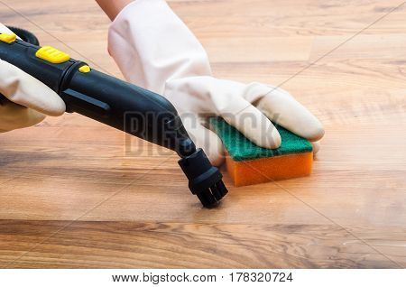 Wooden parquet laminate floors cleaning with steam in the room. Regular clean up. Cleaning concept