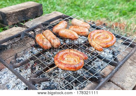 Delicious sausages on a metal grid grilling over hot coals for a picnic lunch on a summer vacation