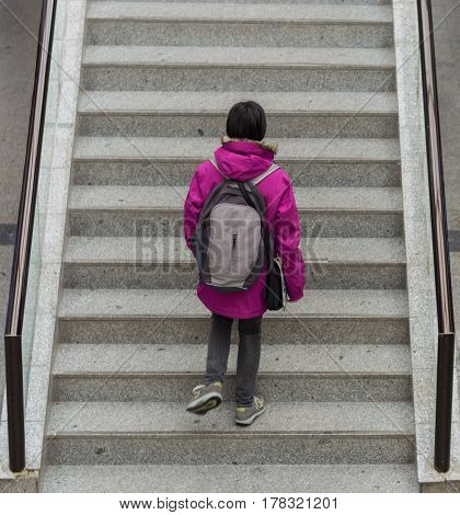 Young woman climbing the stairs in a covered market