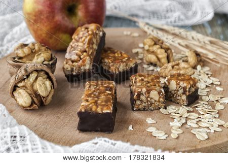 Confectionery from nuts and dried fruits on a wooden board