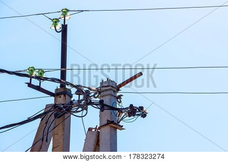 Electric poles, insulators and wire close up on blue sky background