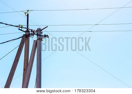 Electric poles, insulators and wire on blue sky background