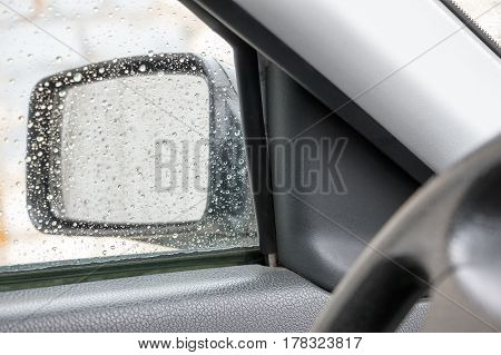 View of the rear view mirror on a rainy day from inside the car
