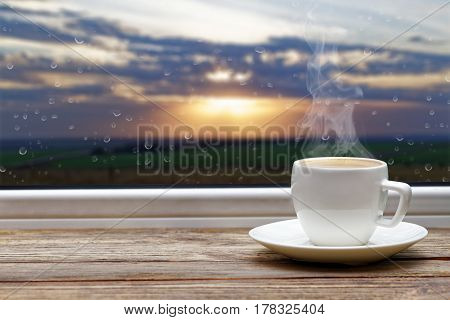 White steaming cup of hot coffee on vintage wooden windowsill or table against window with raindrops and sunset on blurred background. Shallow focus.