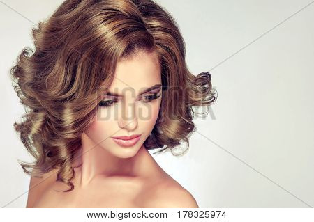 Girl with  shiny wavy medium length hair . Beautiful model with curly hairstyle .
