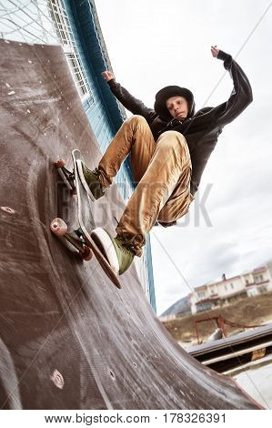 A teenage skater in a sweatshirt and jeans rides the wall on a skateboard in a skatepark, a wide-angle