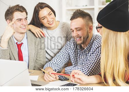 Attractive young males and females at workplace looking at laptop screen together. Team working on project. Teamwork concept
