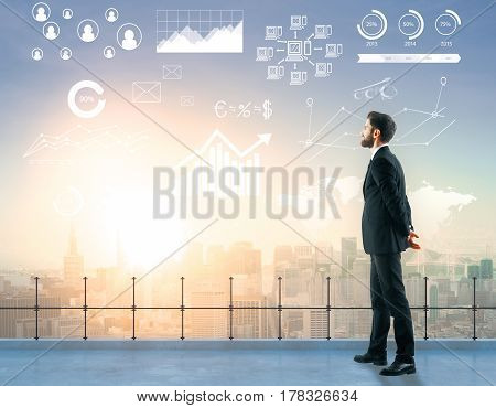 Side view of handsome young man standing on rooftop with digital charts globe HR and other icons. City view background. Global business concept