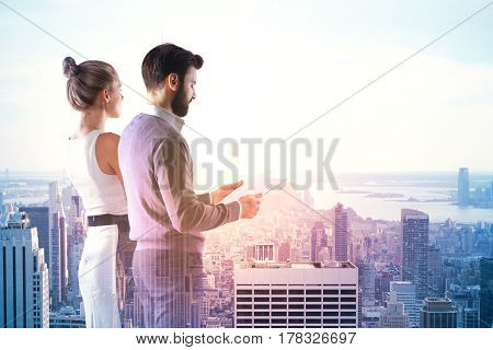 Side view of attractive young businessman and woman reading contract terms and conditions on city background. Double exposure. Teamwork concept