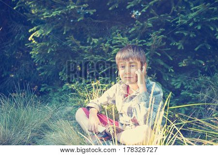 Happy Boy In Headphones Sits And Listens To Music In The Lush Grass In A Forest Glade On A Sunny Eve