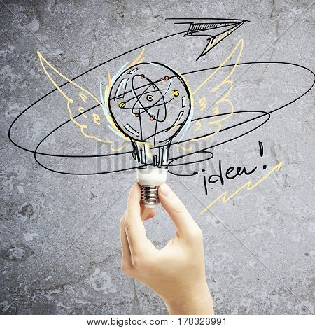 Hand holding lamp on concrete background with drawn wings and arrow. Success and idea concept