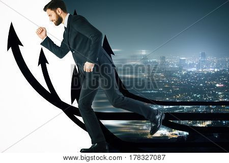 Side view of running young businessman with upward arrows on night city background. Success concept
