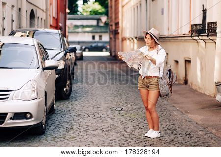 Travel guide. Young female traveler with backpack and with map on the street. Travel concept.