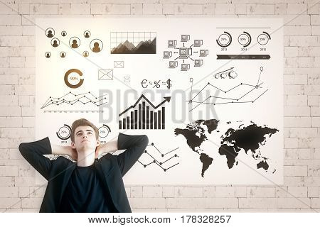 Relaxing european man on brick background with business charts in frame. Financial growth concept