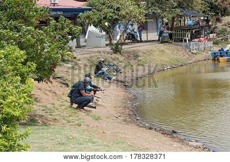 SAN JOSE, COSTA RICA-MARCH 04, 2017: Fisher on the shore of the lake at La Sabana Park in San Jose, Costa Rica