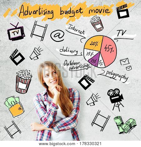 Attractive young woman on concrete background with cinematography related drawings. Advertising budget movie concept