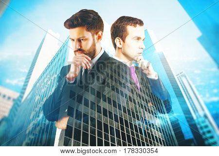Two handsome thoughtful businessmen on blue city background. Teamwork concept. Double exposure