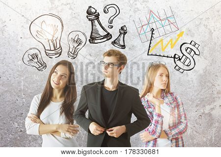 Attractive young businessman and women with creative drawn lamps charts dollar sign and chess figures on concrete background. Teamwork concept