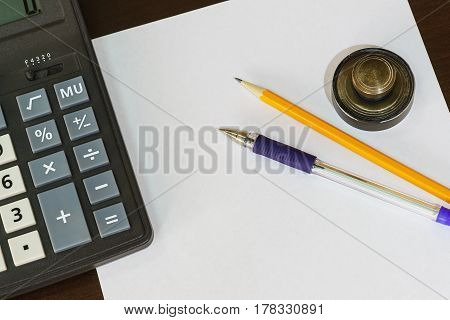 Calculator print pen and pencil lying on a blank sheet of paper. The creation of new enterprises