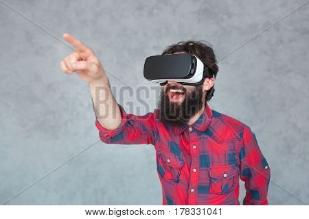 Laughing man touching the air during the virtual reality experience. Horizontal studio shot.