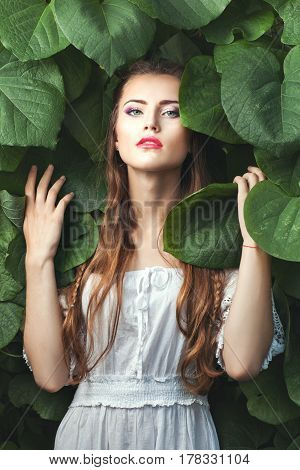 Portrait of a beautiful and tender woman among the green foliage of trees in nature.