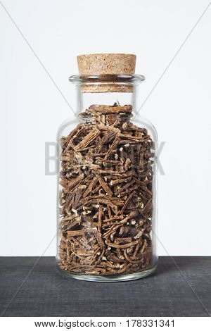 Dried dandelion roots herb inside a glass jar. Herbs and plants for tea.