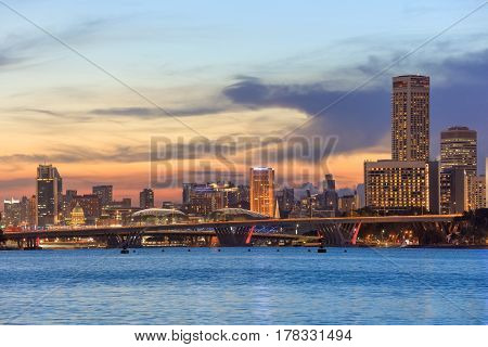 view of central Singapore with Flyer observation wheel and water on foreground. Modern city architecture at sunset
