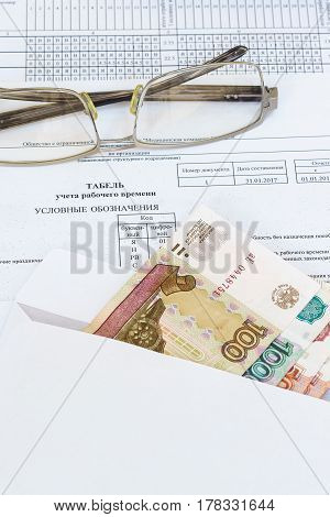 Glasses and an envelope with ruble bills lying on the sheet of accounting of working time. Payroll. Russia
