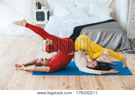 Husband and wife perform sports exercises in the morning in their own bedroom.