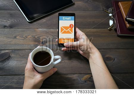 The woman received an e-mail online on a mobile phone. Message online icon. The mobile phone is in female hands. Dark brown wooden background. Diaries, tablet pc. Modern devices at home. Woman using the touch screen.