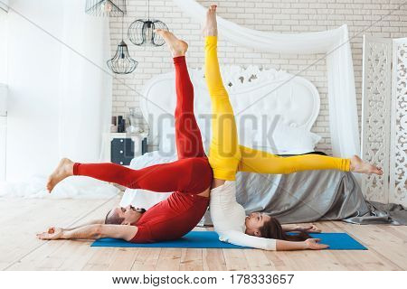 Sports stand on the head a married couple is engaged in yoga in the morning.