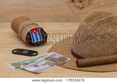 Siesta - cigars straw hat and Cuban banknotes on a wooden table