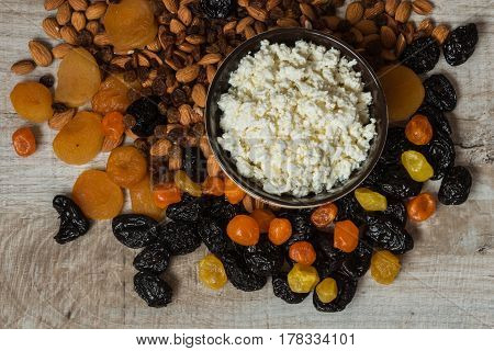 Cottage Cheese In White Dish. Prunes, Dried Apricots, Dried Mandarins And Almonds On A Light Wooden