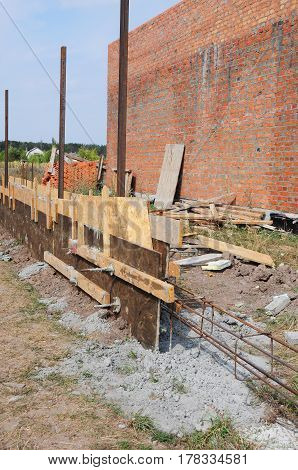 Fence foundation construction. Rebar steel bars reinforcement concrete bars with wire rod and wooden formwork for fence foundation.