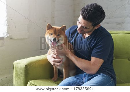 Young hansome caucasian man wearing blue t-shirt sitting on green sofa hugging snuggling and looking on his lovely Shiba Inu dog and smiling at home. Close friendship between owner and pet.