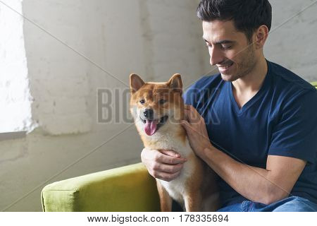 Portrait of young attractive european male sitting on the couch at home with his best friend shiba inu dog looking on his cute pet stroking and petting. Concept of friendship togetherness.