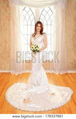 portrait bride standing in front of window